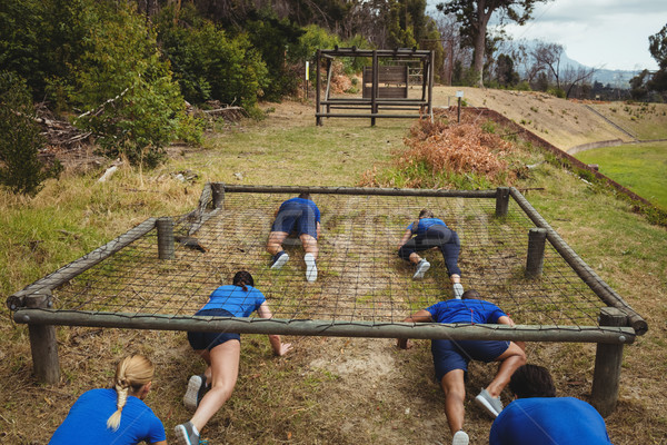 Fit people crawling under the net during obstacle course Stock photo © wavebreak_media