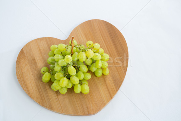 Overhead of green bunch of grapes on chopping board Stock photo © wavebreak_media