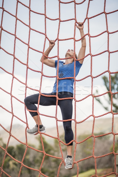 Fit woman climbing a net during obstacle course Stock photo © wavebreak_media