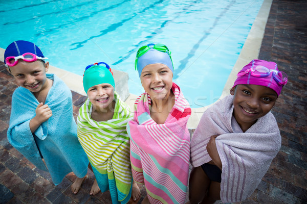 Little swimmers wrapped in towels standing at poolside Stock photo © wavebreak_media