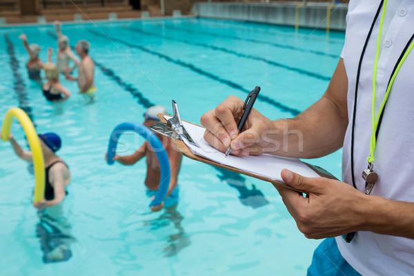 Swim coach writing on clipboard near poolside Stock photo © wavebreak_media