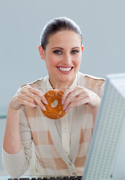 Jonge zakenvrouw eten donut bureau computer Stockfoto © wavebreak_media