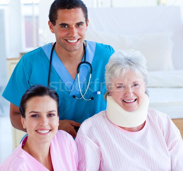 Two smiling doctors taking care of an injured senior woman Stock photo © wavebreak_media