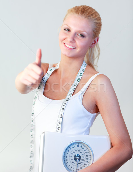 Attractive woman with thumb up holding a scales focus on woman Stock photo © wavebreak_media