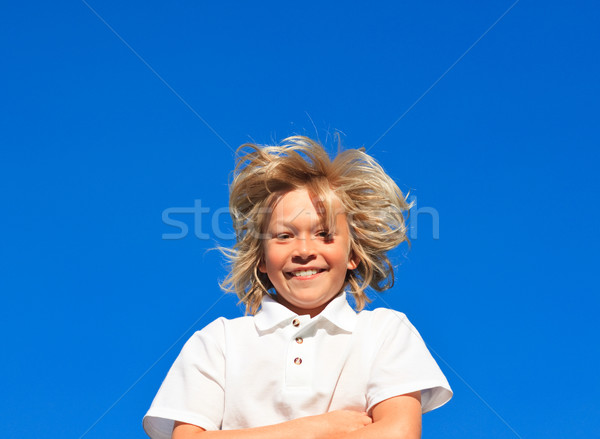 Smiling Kid with arms folded having fun outdoor  on a blue sky background Stock photo © wavebreak_media