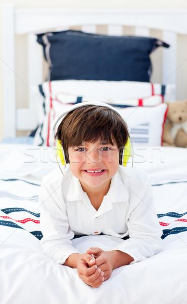 Сток-фото: улыбаясь · мало · мальчика · прослушивании · музыку · наушники