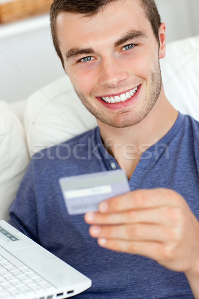 Close-up of a jolly man holding a card and a laptop Stock photo © wavebreak_media