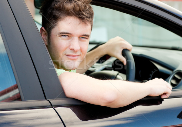 Happy young male driver sitting in his car and looking out of the window Stock photo © wavebreak_media