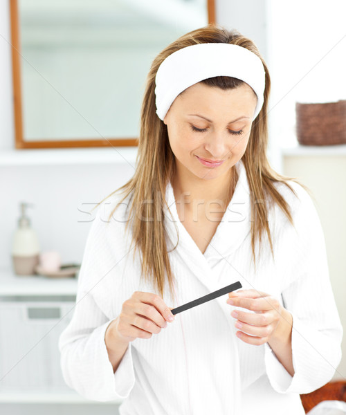 Positive woman using a nail file wearing a bath robe standing in the bathroom at home Stock photo © wavebreak_media