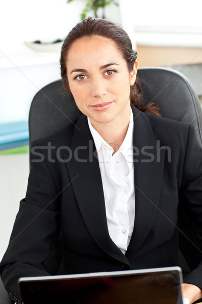 Self-assured hispanic businesswoman sitting at her desk in front of her laptop in her office Stock photo © wavebreak_media