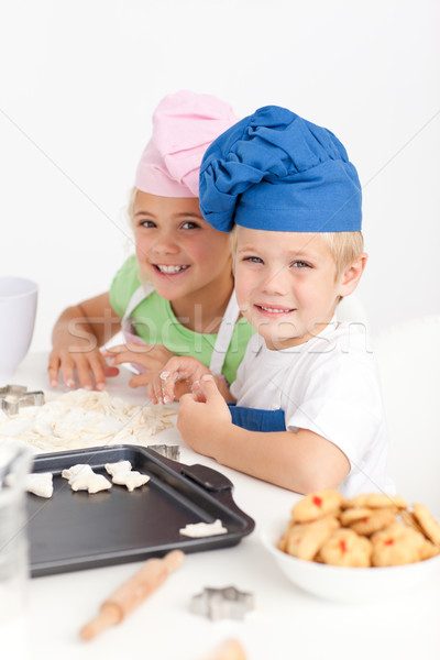Adorable siblings kneading together a dough in the kitchen to make cookies Stock photo © wavebreak_media