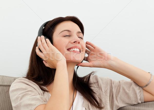 Happy woman enjoying a song on the sofa at home Stock photo © wavebreak_media
