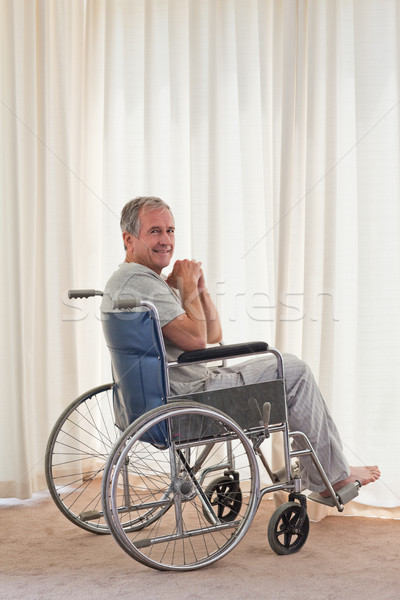 Smiling man in his wheelchair at home Stock photo © wavebreak_media
