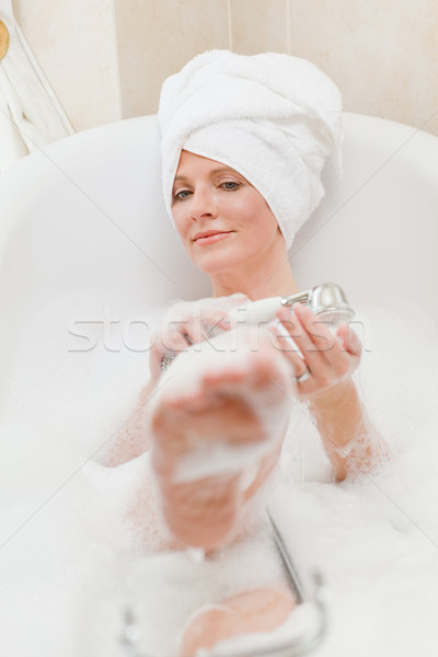 Smiling woman taking a bath with a towel on her head  Stock photo © wavebreak_media
