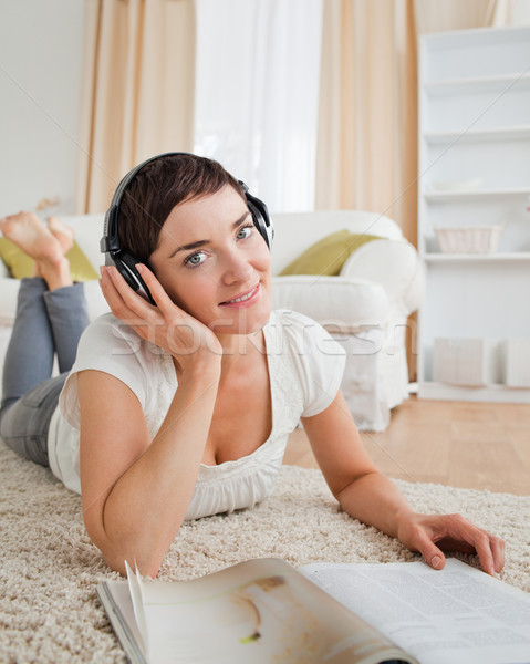 Portrait of a smiling woman with a magazine enjoying some music while lying on a carpet Stock photo © wavebreak_media