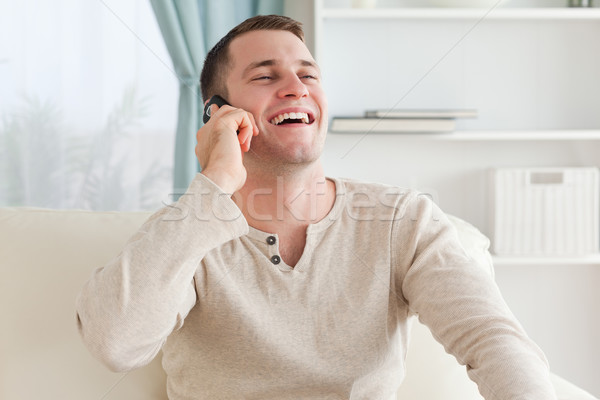 Laughing man making a phone call while sitting on a couch in his living room Stock photo © wavebreak_media