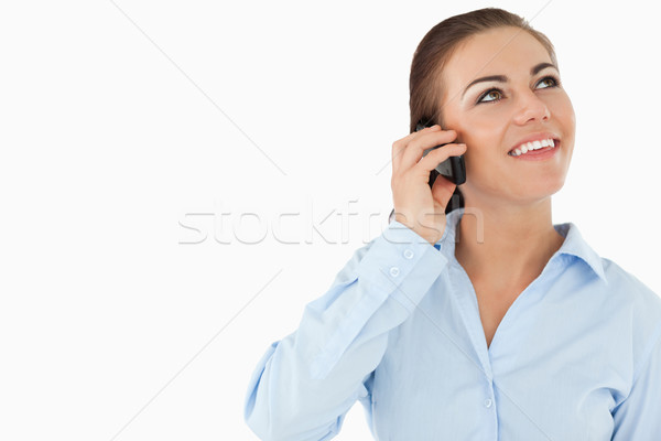 Stock photo: Smiling businesswoman looking upwards while on the phone against white background