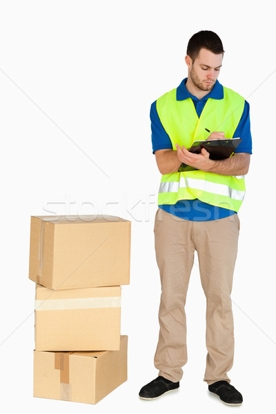 Young delivery man filling in delivery note against a white background Stock photo © wavebreak_media