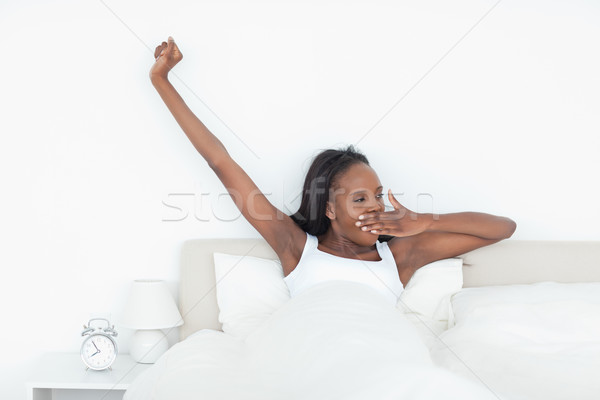 Woman stretching her arms and yawning in her bedroom Stock photo © wavebreak_media