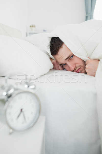 Portrait of a man covering his ears while his alarm clock is ringing in his bedroom Stock photo © wavebreak_media