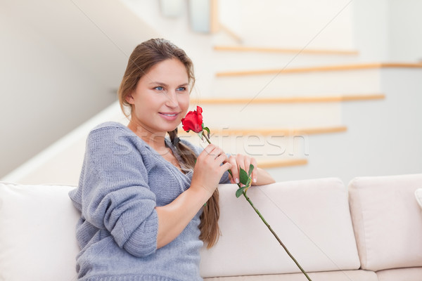 Young woman smelling a rose in her living room Stock photo © wavebreak_media