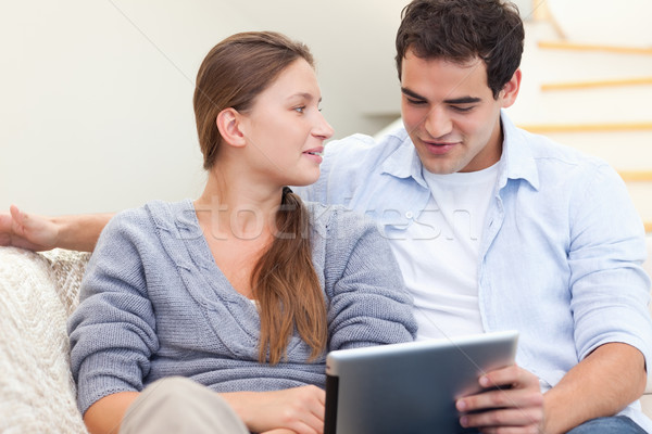 Engaged couple using a tablet computer in their living room Stock photo © wavebreak_media