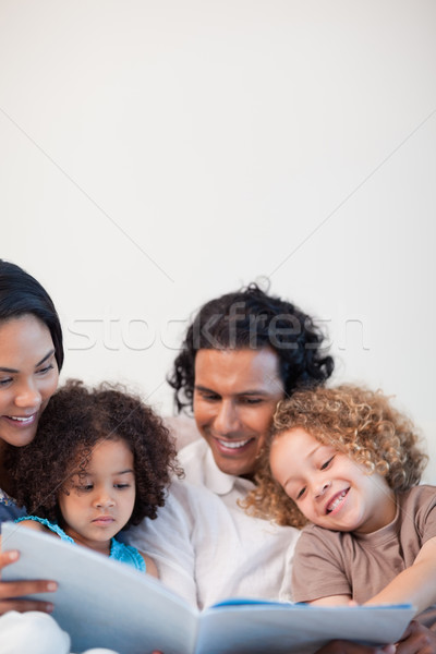 Cheerful young family on the sofa looking at photo album together Stock photo © wavebreak_media