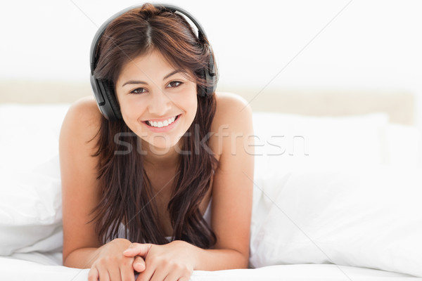 A smiling woman with her head tilted and listening to music at the end of the bed.  Stock photo © wavebreak_media