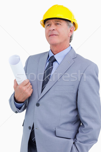 Mature architect wearing helmet and holding plans against a white background Stock photo © wavebreak_media