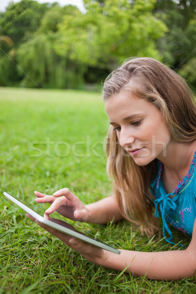 Serious student lying on the grass in a park while using her tablet computer Stock photo © wavebreak_media
