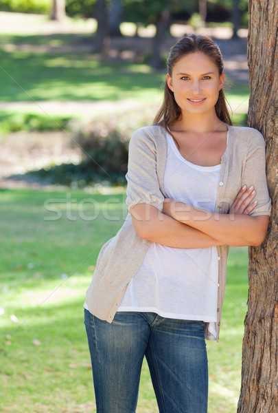 Smiling woman with her arms crossed leaning against a tree Stock photo © wavebreak_media