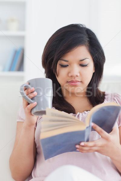 женщину кружка чтение книга гостиной Сток-фото © wavebreak_media