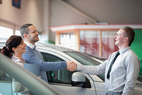 Salesman smiling while shaking the hand of a customer in a car shop Stock photo © wavebreak_media
