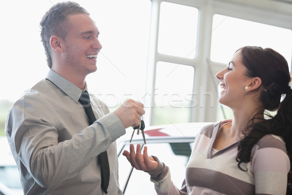 Stock photo: Laughing salesman giving keys to a woman in a car shop