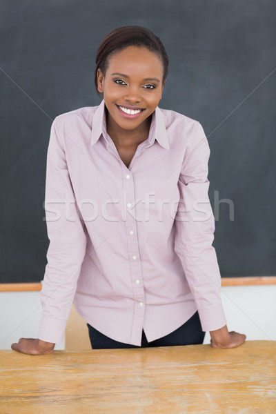 Teacher standing up while smiling in a classroom Stock photo © wavebreak_media