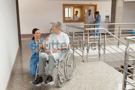 Nurse talking with child in wheelchair and neck brace with mother in hospital corridor Stock photo © wavebreak_media