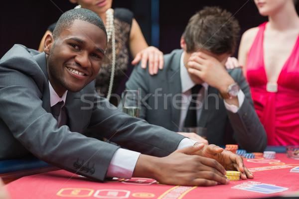 Hombre sonriendo bote póquer juego casino Foto stock © wavebreak_media