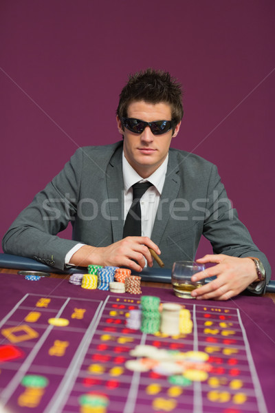 Man wearing sun glasses at roulette table drinking whiskey and smoking cigar Stock photo © wavebreak_media
