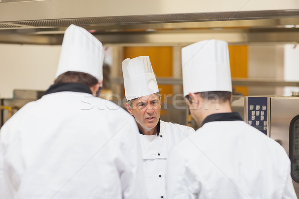 Angry head chef scolding employees in the kitchen Stock photo © wavebreak_media