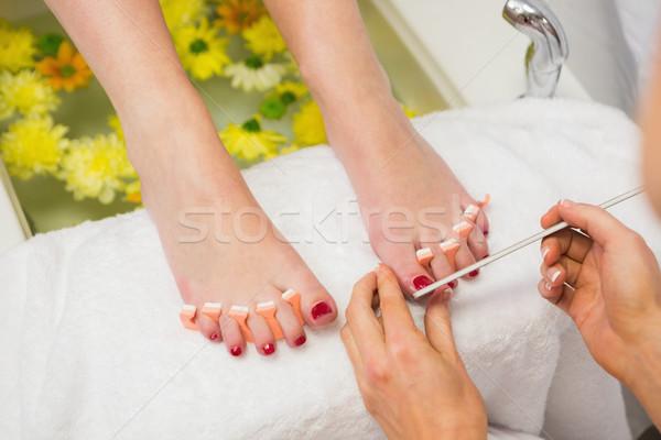 Woman polishing toe nails at spa center Stock photo © wavebreak_media