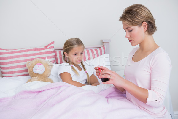 Mother about to give medicine to sick daughter Stock photo © wavebreak_media