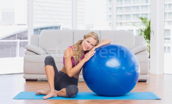 Toned blonde sitting beside exercise ball smiling at camera Stock photo © wavebreak_media