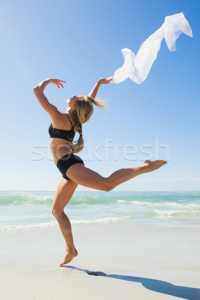 Fit blonde jumping gracefully with scarf on the beach Stock photo © wavebreak_media