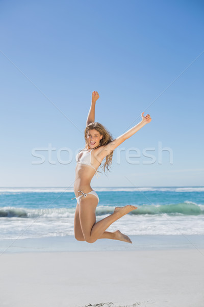 Fit smiling woman in white bikini leaping on beach Stock photo © wavebreak_media
