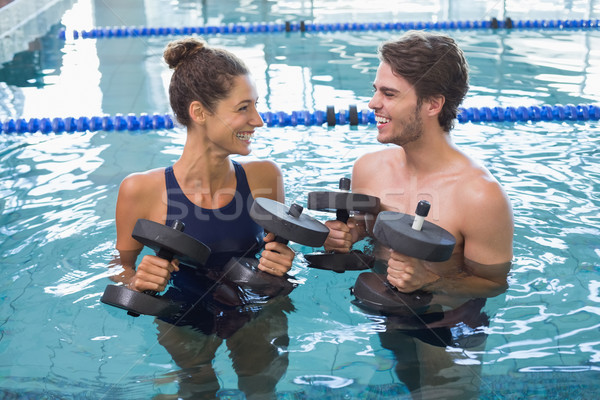 Man and woman standing with foam dumbbells in the pool Stock photo © wavebreak_media