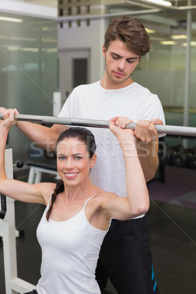 Fit smiling woman lifting barbell with her trainer spotting Stock photo © wavebreak_media