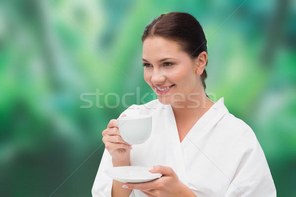 Beautiful brunette in bathrobe drinking herbal tea Stock photo © wavebreak_media