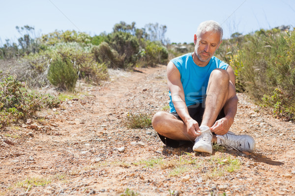 Smiling jogger tying his shoelace on mountain trail Stock photo © wavebreak_media