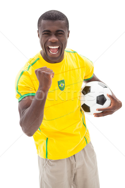 Excited brazilian football fan cheering holding ball Stock photo © wavebreak_media
