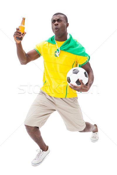 Happy brazilian football fan holding ball and beer Stock photo © wavebreak_media